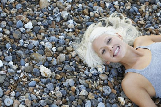 Young woman smiling lying on pebble beach view from above