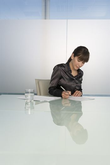 Young businesswoman writing at desk in office