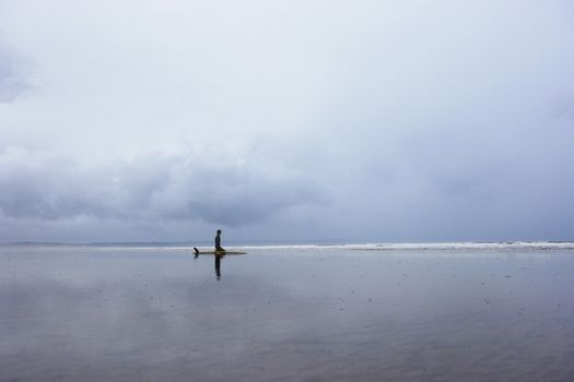 Lone surfer sitting on surfboard in shallow water side view