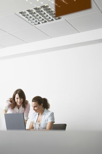 Young businesswomen discussing over laptop at meeting in office