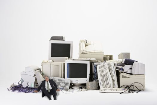 Digital composite of businessman sitting by various obsolete technologies against white background