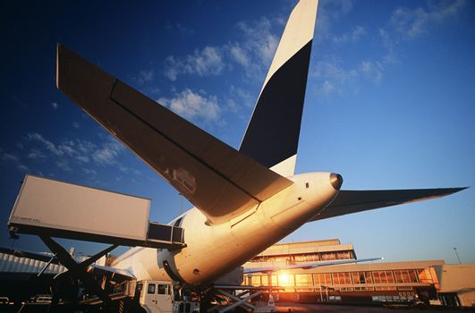 Tail fin of airplane at airport sunset