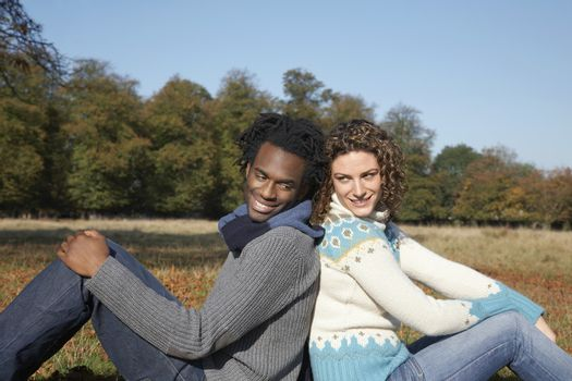 Couple sitting back to back in field side view