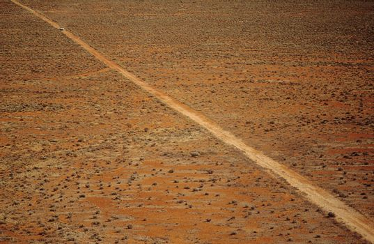 Car driving along desert road outback Australia