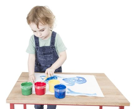 cute child making painting on small desk. studio shot isolated on white background