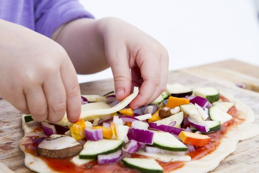 small hands preparing fresh pizza with many vegetables
