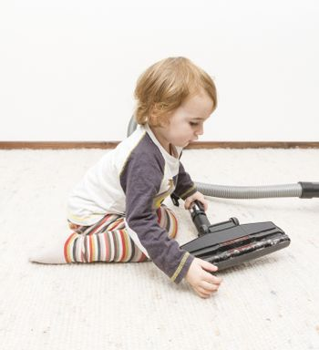 young child sitting next to vacuum cleaner