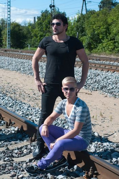 Shot of two men on train tracks, focus on man in black