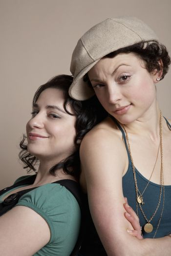 Two young women back to back portrait