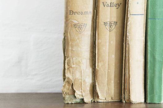 Stack of old books on wooden chest close up