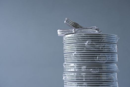 Stack of plates and cutlery wrapped in plastic