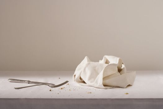 Dish cloth cutlery and crumbs on table