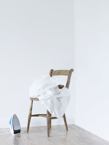 Laundry stacked on chair next to iron