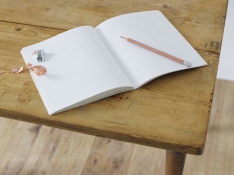 Open notebook with pencil and pencil sharpener on table elevated view