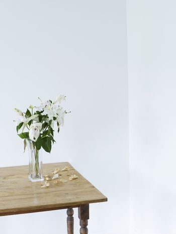 White lilies in vase on table elevated view