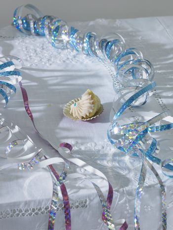 Unfinished cup cake amongst streamers on table elevated view