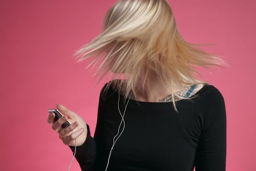 Young woman tossing hair while listening to music through MP3 played on pink background
