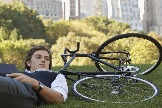 Man leaning against bicycle on lawn