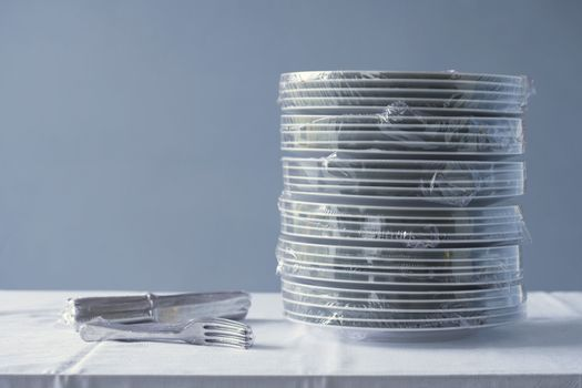 Stack of plates and cutlery wrapped in plastic on table