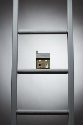 Small model of house on ladder