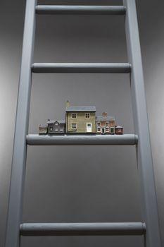 Small model houses on ladder