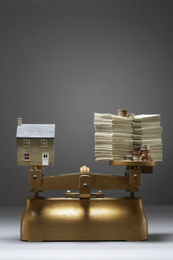 Model house and money on scales