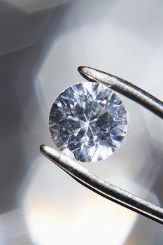 Diamond held by tweezers close-up