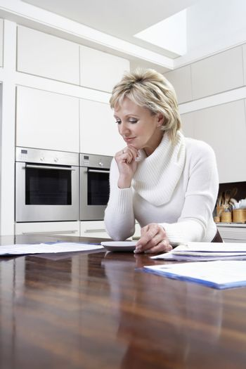 Middle aged woman calculating domestic bills with calculator in kitchen