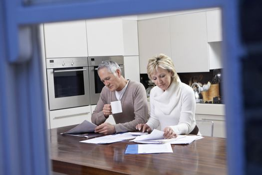 Middle aged couple calculating their domestic bills at kitchen table