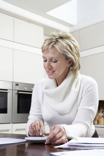 Happy middle aged woman calculating domestic bills with calculator in kitchen