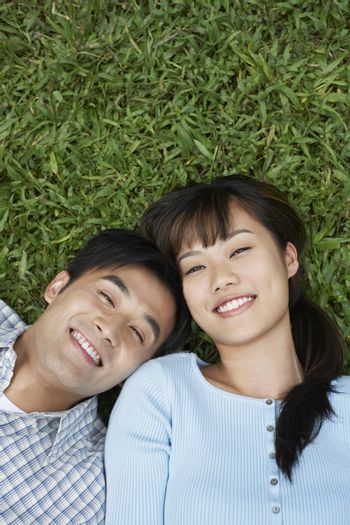 Elevated view of happy couple lying on grass