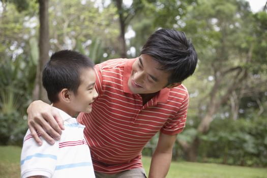 Happy father and son arm around in park