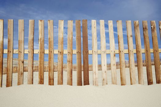 Wooden fence at beach against cloudy sky