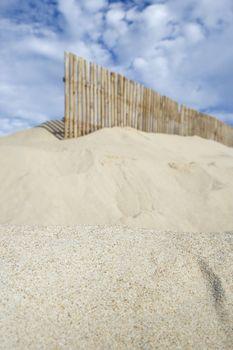 Wooden fence on sandy beach against cloudy sky