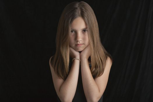 Portrait of young brunette girl resting chin in hands against black background