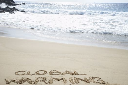 Global warming written in the sand at beach