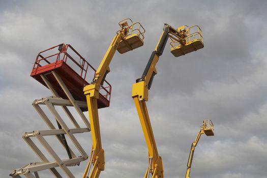 Hydraulic lift machines against stormy sky