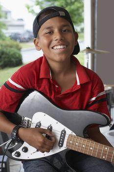 Boy (10-12) with electric guitar in garage portrait