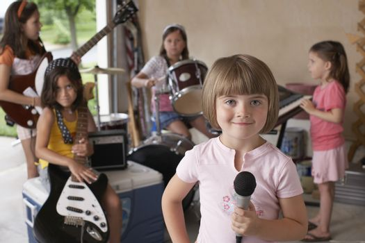Group of girls (7-9) with instruments in garage