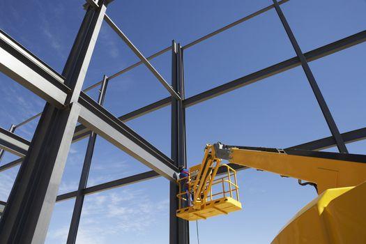Welder working from cherry picker on steel framing structure