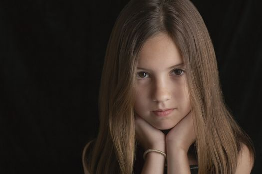 Portrait of young brunette girl resting chin on hands against black background