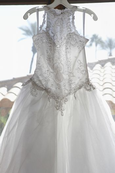 Beautiful bridal dress hanging by window