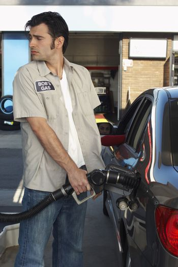 Gas station worker refueling car at petrol station