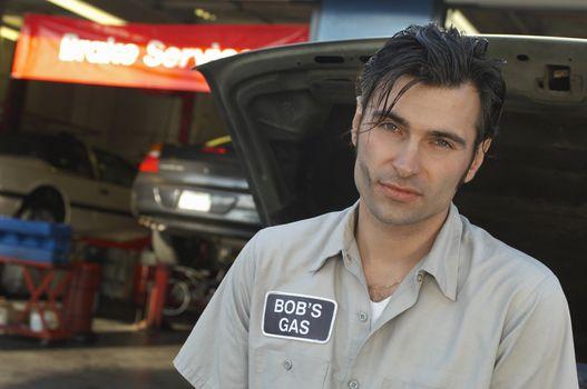 Portrait of a garage worker by open car hood