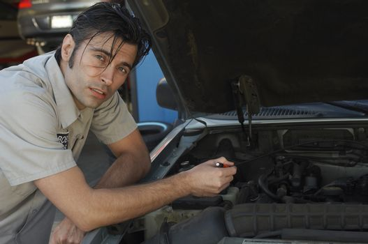 Portrait of a mechanic repairing the engine of car