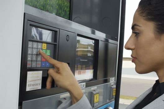 Beautiful young woman pushing buttons on gasoline fuel pump