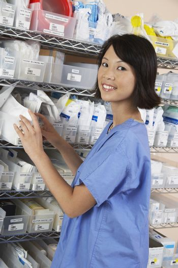 Portrait of female standing at shelf with medicines