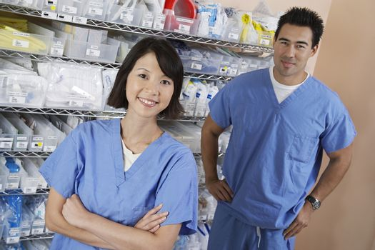 Portrait of female and male nurse standing by shelves with medical supply