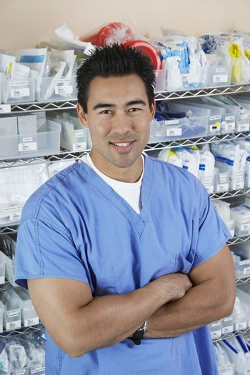 Portrait of male nurse standing by shelves with medical supply