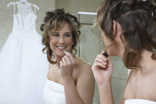 Bride applying lipstick in mirror